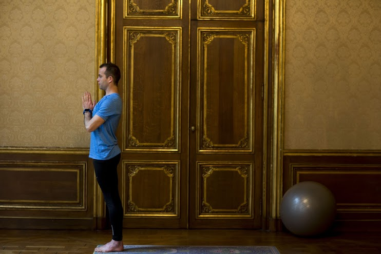 Debout, pieds joints, dos bien droit et mains en prière au niveau du plexus. EXPIRER.